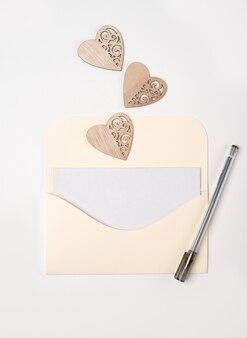Una busta con all'interno un foglio di carta bianco, una penna e cuori di legno sullo sfondo chiaro (bianco)