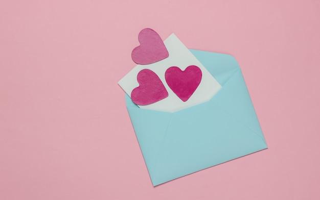 Busta con una lettera, cuori decorativi su sfondo giallo. mockup piatto per san valentino, matrimonio o compleanno.