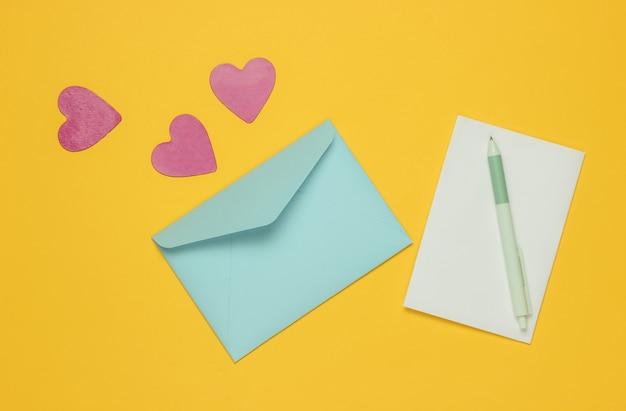 Busta con una lettera, penna, cuori decorativi su sfondo giallo. mockup piatto per san valentino, matrimonio o compleanno.