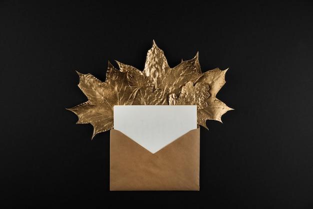 Busta con lettera e foglie di acero dorate lucide su sfondo nero