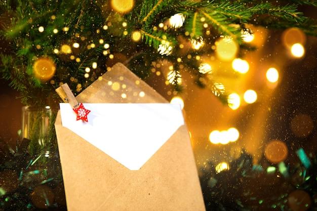 Busta con foglio di carta- lettera a babbo natale, copia spazio su uno sfondo natalizio di luci sfocate in bokeh, ghirlande, rami di abete. molletta-stella. anno nuovo, lista dei desideri, sogno, regali