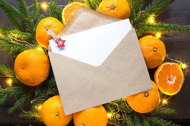 Busta con un foglio di carta, una lettera a babbo natale, copyspace su uno sfondo natalizio di mandarini, ghirlande, rami di abete. stella molletta per appunti. anno nuovo, lista dei desideri, sogno, regali