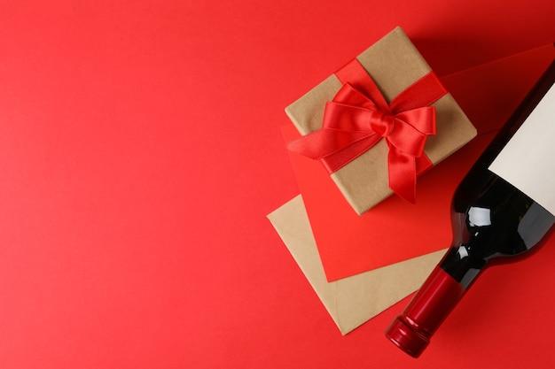 Buste, confezione regalo e bottiglia di vino su sfondo rosso