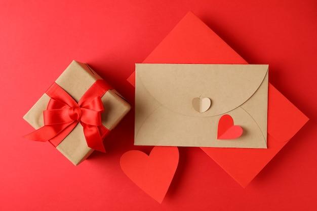 Buste, cuori e confezione regalo su sfondo rosso
