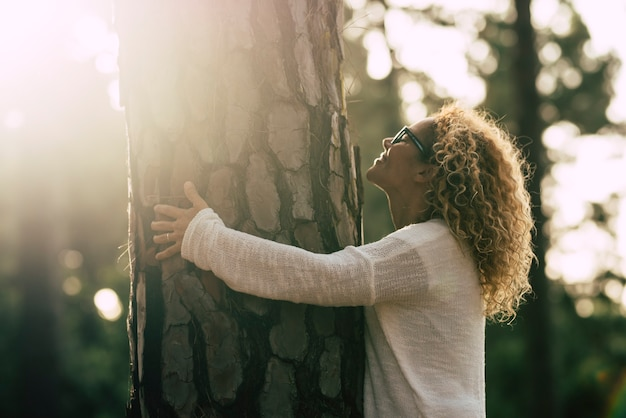 Il concetto di ambiente con una bella donna riccia bionda adulta abbraccia e aiuta un grande pino nella foresta