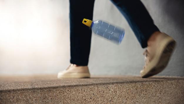Ambiente, cura dell'ecologia, concetto di problema dei rifiuti di plastica. una persona ha fatto cadere una bottiglia di plastica usata nel pavimento pubblico. inquadratura dal basso. concentrarsi sulla bottiglia