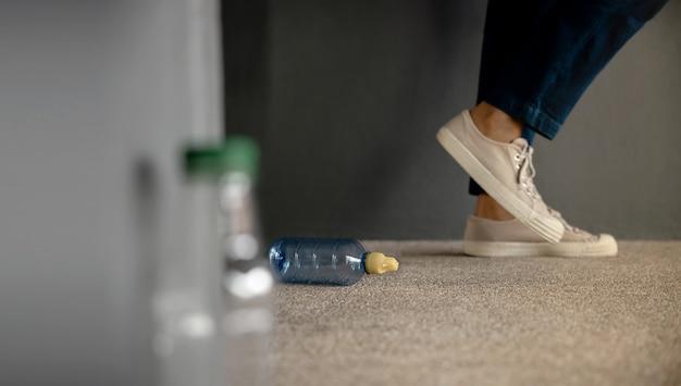 Ambiente, cura dell'ecologia, concetto di problema dei rifiuti di plastica. persona che sporca una bottiglia di plastica usata nel pavimento pubblico. inquadratura dal basso. concentrarsi sulla bottiglia