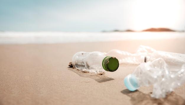 Ambiente, cura dell'ecologia, concetto rinnovabile. rifiuti di bottiglie di plastica sulla sabbia della spiaggia