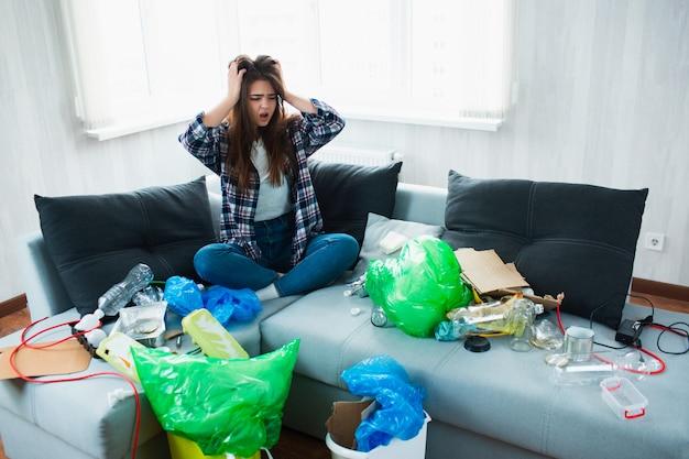Concetto di inquinamento ambientale. giovane donna scioccata. non sa cosa fare dell'inquinamento del suo appartamento e del mondo intero
