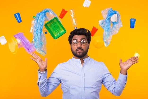Inquinamento ambientale, problema di riciclaggio della plastica e concetto di smaltimento dei rifiuti - uomo indiano sorpreso ha alzato le braccia ai lati su sfondo giallo con spazzatura