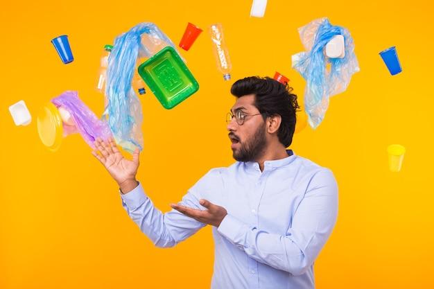 Inquinamento ambientale, problema di riciclaggio della plastica e concetto di smaltimento dei rifiuti - uomo indiano sorpreso su sfondo giallo con spazzatura.