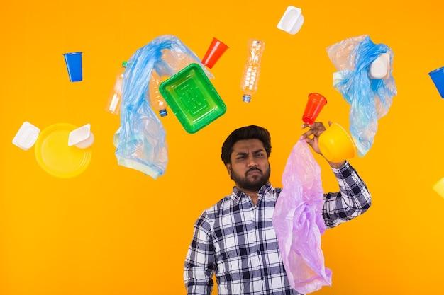 Inquinamento ambientale, problema di riciclaggio della plastica e concetto di smaltimento dei rifiuti - uomo indiano sconvolto che tiene il sacco della spazzatura su sfondo giallo.