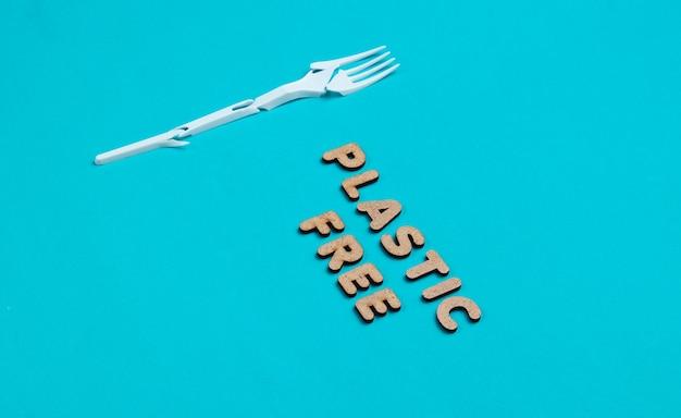 Natura morta ecocompatibile. forchetta di plastica rotta su sfondo blu con la parola eco.