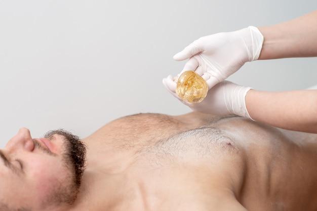 Petto di epilazione del giovane maschio con pasta di cera liquida dalle mani del cosmetologo femminile nel salone di bellezza
