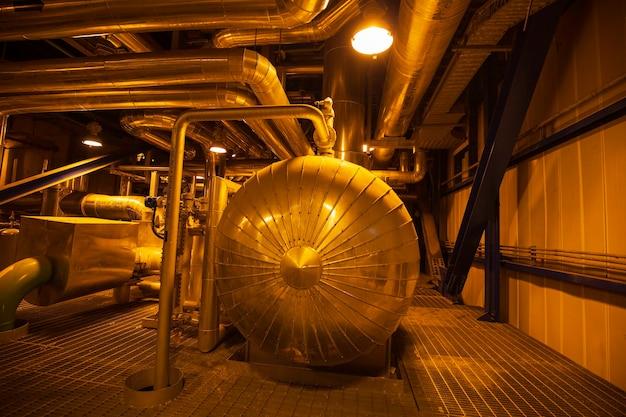 Isolamento di apparecchiature, cavi e tubazioni del tamburo del vapore come si trova all'interno della centrale elettrica della sala di controllo industriale