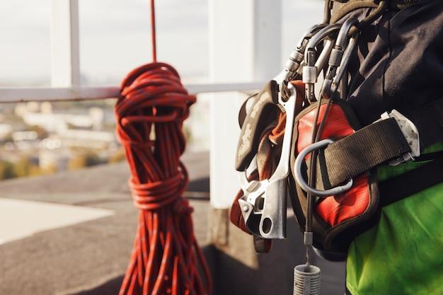 Attrezzature di alpinismo industriale lavoratore sul tetto dell'edificio durante il lavoro industriale a molti piani. attrezzatura da arrampicata prima di iniziare il lavoro. accesso operaio su corda. concetto di opere urbane. copia spazio