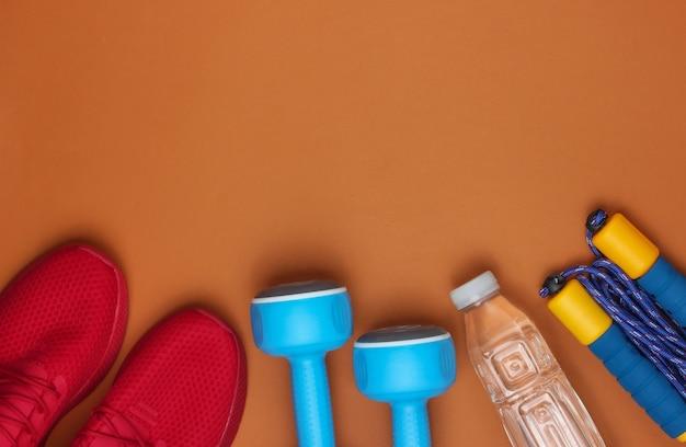 Attrezzature per la formazione su sfondo marrone. scarpe sportive, corda per saltare, manubri, bottiglia d'acqua. stile piatto. copia spazio
