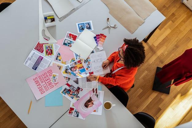 Ampio monolocale attrezzato. insolita donna riccia brillante che si ispira ai ritagli di riviste mentre disegna nuovi design