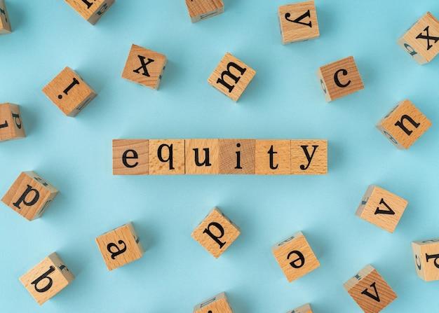 Parola di equità sul blocco di legno. vista piatta su sfondo blu.