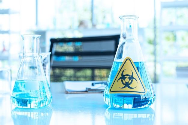 Beuta di erlenmeyer e fluido blu all'interno con segnaletica panoramica di pericolo di attenzione sul tavolo di prova.