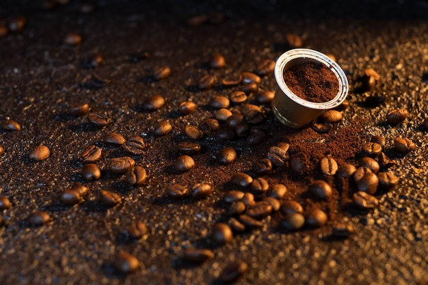 Capsule di caffè espresso sulla superficie del legno con alcuni chicchi di caffè tostati