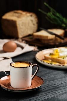 Primo piano del caffè espresso sulla tavola di legno nera. contro il muro sfocato, uovo alla coque (in camicia) in fetta di pane, ricoperto di crema di burro ed erbe aromatiche e pagnotta di pane a fette. idea per la colazione