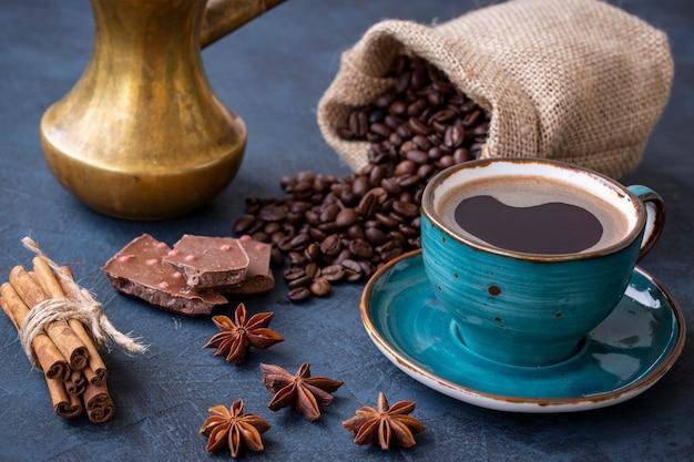 Caffè espresso chicchi di caffè cannella al cioccolato e anice stellato su un tavolo scuro