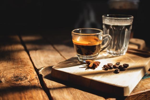 Caffè espresso e acqua fredda su un vecchio tavolo di legno.