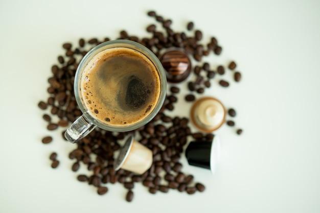 Caffè espresso in una tazza che circonda con chicchi di caffè tostato medio scuro e capsula di caffè da vicino con spazio di copia.