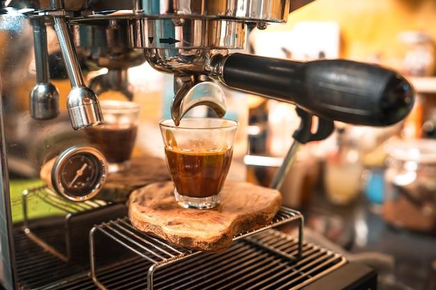 Il caffè espresso sta scorrendo nella tazza del colpo.