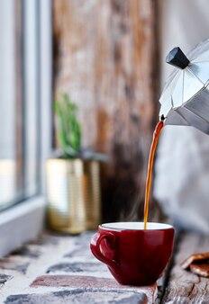 Il caffè espresso viene versato da una caffettiera geyser in una tazza rossa. il vapore sale sopra la tazza. primo piano, fuoco selettivo