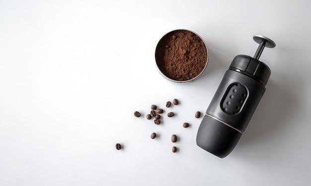 Macchina per caffè espresso, tazza e fagioli sul tavolo bianco. vista dall'alto