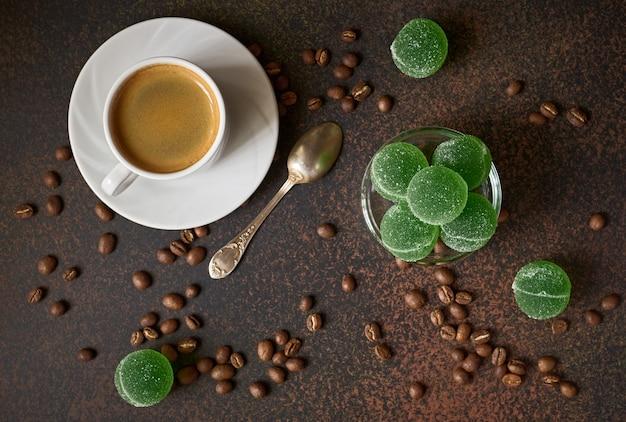 Caffè espresso, marmellata di frutta e chicchi di caffè fritti freschi sul tavolo scuro