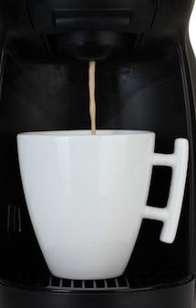 Macchina per caffè espresso che versa il caffè in tazza bianca