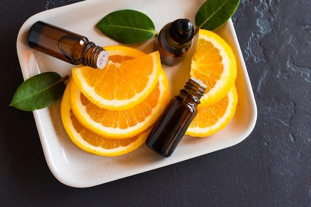 Olio essenziale aromatico di arancia con agrumi su vassoio in ceramica e fondo nero. vista dall'alto.