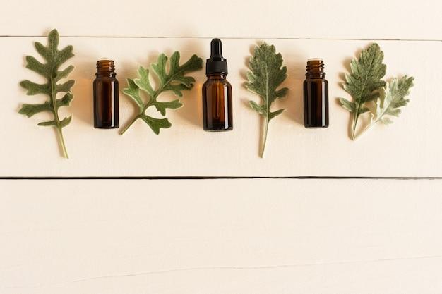 Olio aromatico essenziale con ingredienti naturali sullo sfondo di un tavolo in legno bianco con foglie grigie di piante. posa piatta.