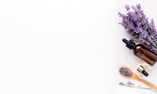 Olio essenziale di lavanda con fiori di lavanda su sfondo bianco. banner, piatto, vista dall'alto, copia spazio.