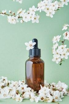 Bottiglia di olio essenziale con ramo di piante in fiore su sfondo verde