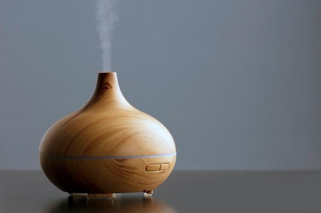 Bottiglia di olio essenziale con un umidificatore elettrico ad ultrasuoni che emette goccioline d'acqua atomizzata