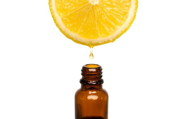 Gocciolamento di olio essenziale di limone su sfondo bianco
