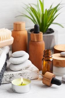 Olio essenziale in bottiglie riutilizzabili su fondo in legno. spa biologica naturale con packaging ecologico
