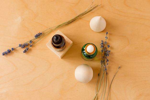 Olio essenziale con contagocce e rami di lavanda su fondo in legno con cubetti di legno. flacone cosmetico in vetro marrone e verde, siero. vista dall'alto.