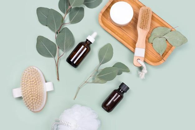Oli essenziali, contenitore per creme per il viso e spazzole da massaggio con foglie di eucalipto naturali su sfondo verde