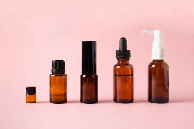Oli essenziali, varie bottiglie aromaterapia su uno sfondo rosa. concetto di aromaterapia e profumi