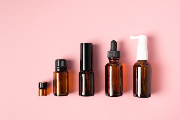 Oli essenziali, aromaterapia di varie bottiglie su una superficie rosa. concetto di aromaterapia e profumi