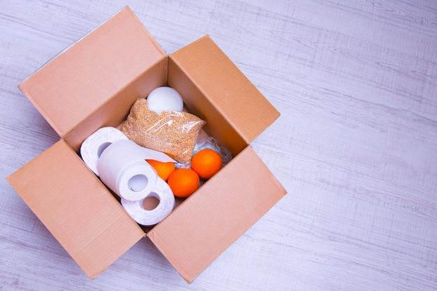 Prodotti essenziali per l'autoisolamento in una scatola: cereali. carta igienica, frutta, cibo in scatola. consegna a domicilio. assistenza alla popolazione