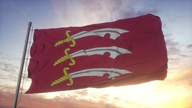 Bandiera dell'essex, inghilterra, che fluttua nel vento, nel cielo e nello sfondo del sole. rendering 3d