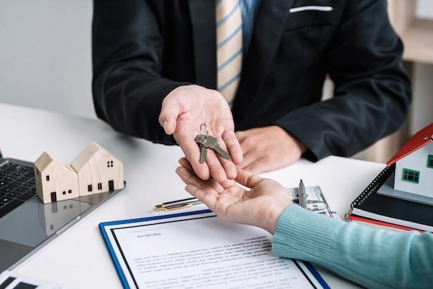 L'agente immobiliare consegna al cliente le chiavi di casa quando l'affare va a buon fine in ufficio.