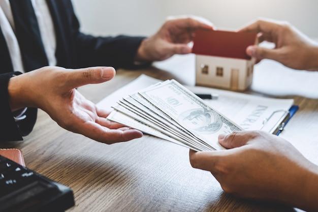 Agente immobiliare che fornisce le chiavi di casa al cliente dopo aver firmato un contratto di contratto immobiliare con modulo di richiesta di mutuo approvato, relativo all'offerta di mutuo ipotecario e all'assicurazione casa