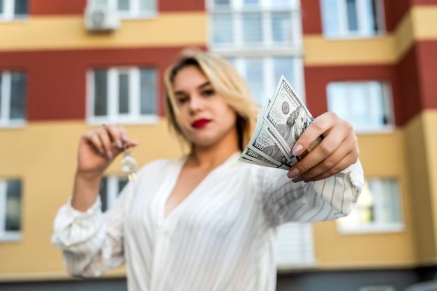 Agente immobiliare che tiene la chiave contro la nuova casa come sfondo. concetto di vendita